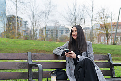 Smiling female professional with coffee cup looking away while holding mobile phone on park bench - p300m2243219 by Mikel Taboada