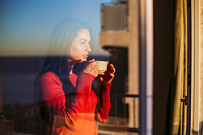Contemplating woman having coffee while looking through window at home - p300m2266646 by DREAMSTOCK1982