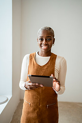 Smiling woman holding digital tablet at home - p300m2277412 by Rafa Cortés