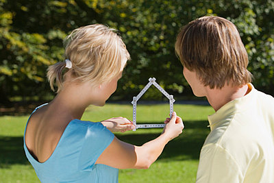 Young couple holding folding ruler shaped as house - p6090049f by PICK photography