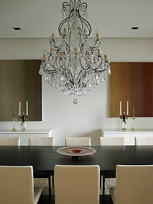 Chandelier above table in dining room in Brazilian home - p855m908925 by Richard Powers
