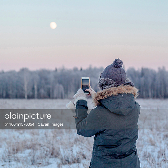 Rear view of woman photographing with smart phone while standing on snowy field during sunset - p1166m1576354 by Cavan Images
