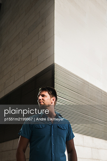 Man stands in front of modern plain facade - p1551m2199967 by André Eikmeyer