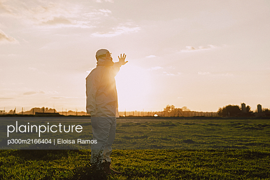 Man wearing protective suit and mask in the countryside at sunset - p300m2166404 by Eloisa Ramos