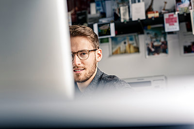 Portrait of young man behind computer screen at desk at home - p300m1535418 by Peter Scholl