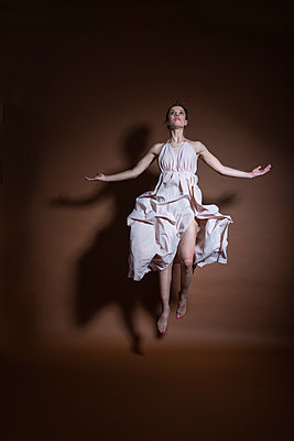 Hovering young woman - p427m2063117 by Ralf Mohr