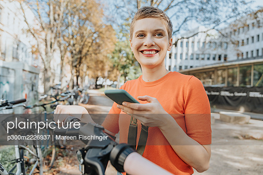 Smiling woman using smart phone while standing on electric push scooter during sunny day - p300m2226937 by Mareen Fischinger