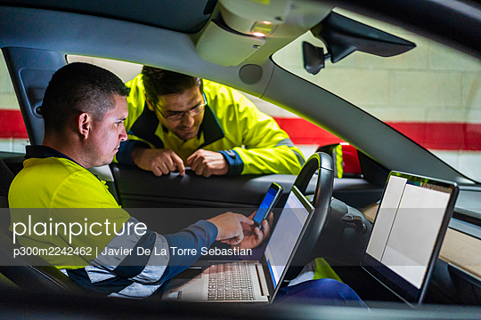Male programmer showing mobile phone to colleague while sitting in electric car - p300m2242462 by Javier De La Torre Sebastian