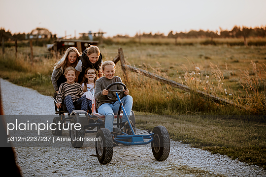 Happy girls riding go-kart on dirt road - p312m2237237 by Anna Johnsson