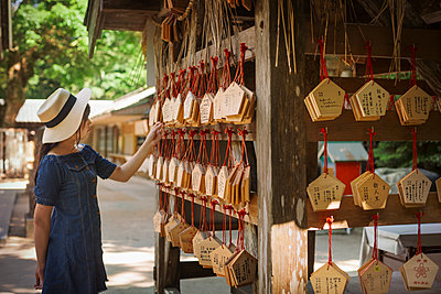 Young woman wearing blue dress looking at wooden fortune telling plaques at Shinto Sakurai Shrine, Fukuoka, Japan. - p1100m1531078 by Mint Images