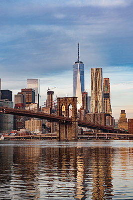 Brooklyn Bridge over East River with cityscape in background against cloudy sky - p1166m1142537 by Cavan Images