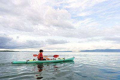Teenager paddling kayak in Costa Rica - p1166m2189656 by Cavan Images
