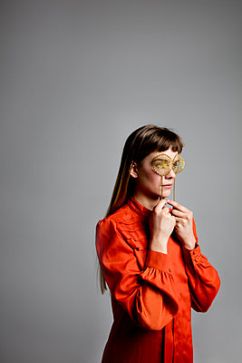 Junge Frau blickt durch Teesiebe - p1212m1092875 von harry + lidy