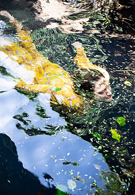 Woman in yellow dress swimming in lake - p1640m2259927 by Holly & John