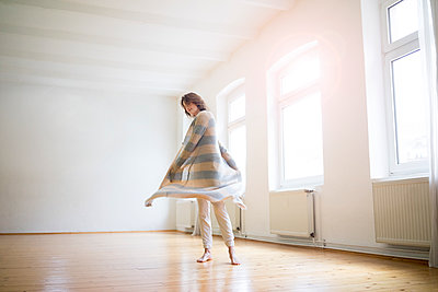 Happy mature woman standing in empty room in sunlight - p300m1562931 by Robijn Page