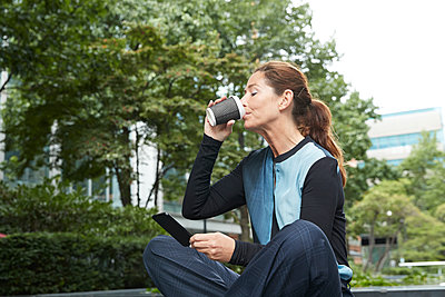 Businesswoman drinking coffee while using mobile phone at office park - p300m2227078 by Pete Muller