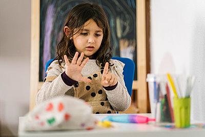 Valencia, Spain. Five-year-old girl doing school homework at home. - p300m2290491 von Ezequiel Giménez