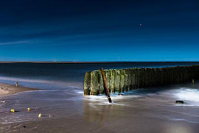 Ocean retaining wall illuminated at night - p301m2148998 by Sebastian Doerken