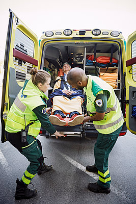 Full length of male and female paramedics unloading patient from ambulance - p426m2118841 by Maskot
