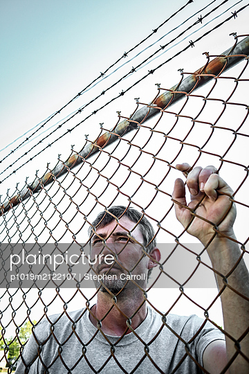 Man behind fence - p1019m2122107 by Stephen Carroll