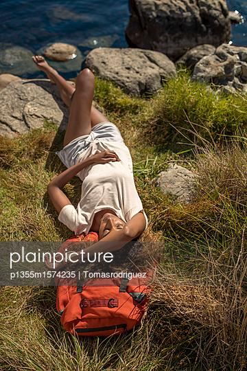 Junge Frau macht eine Pause beim Wandern - p1355m1574235 von Tomasrodriguez