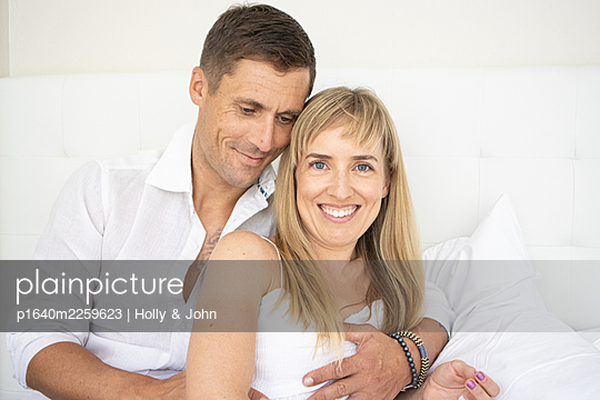 Happy couple sitting on bed, portrait - p1640m2259623 by Holly & John