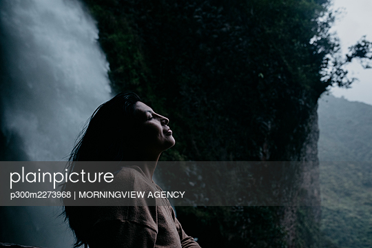Woman with eyes closed standing at waterfall - p300m2273968 by MORNINGVIEW AGENCY