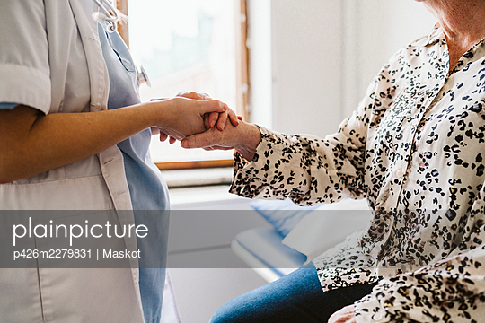 Midsection of female doctor holding senior patient's hand at medical clinic - p426m2279831 by Maskot