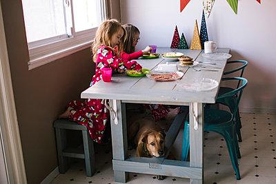 Sisters eating food at table - p1166m1231521 by Cavan Images