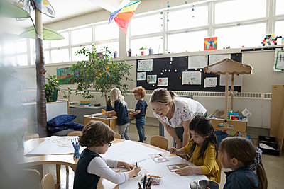 Preschool teacher and students using stencils on poster in classroom - p1192m1560172 by Hero Images