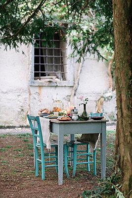 Laid garden table with candles next to a cottage - p300m2068358 von Alberto Bogo