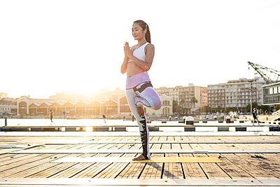 Asian woman practicing yoga on a pier at harbour - p300m2144617 by Rafa Cortés