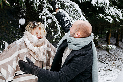 Mature couple with warm clothing having fun in snow by pine trees during vacations - p300m2256100 by Katharina Mikhrin