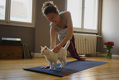 Smiling woman stroking white cat while practicing yoga at home - p301m1579776 by Halfdark