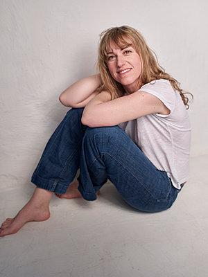 Blonde Frau sitzt im Studio - p885m2200465 von Oliver Brenneisen