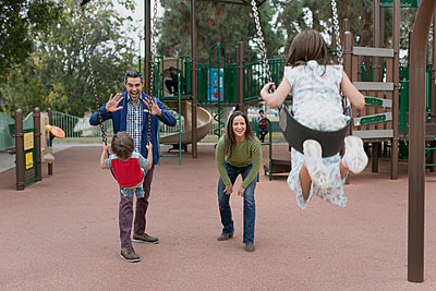 Family playing at swings in park - p924m1422845 by Alyson Aliano