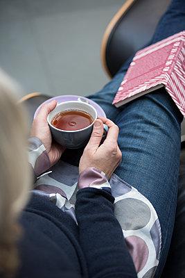 Frau hält Becher mit heissem Tee auf dem Schoß. - p948m2014769 von Sibylle Pietrek