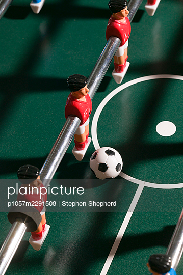 Detail of a table football game showing the plastic players or figures lined up on their bar with an outsize football on the hard green playing surface. - p1057m2291508 by Stephen Shepherd