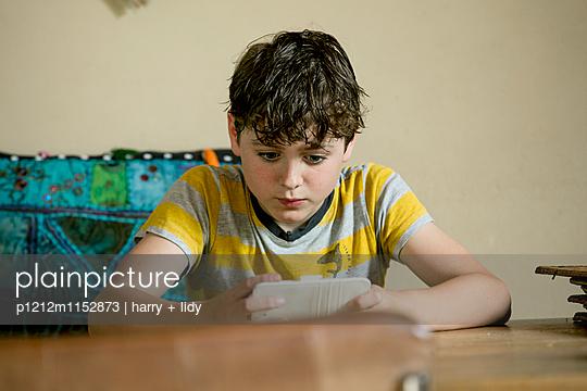 Junge mit dem Smartphone in der Wohnküche - p1212m1152873 von harry + lidy