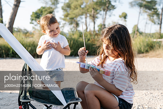 Cheerful baby girl looking at sister painting during sunset - p300m2214084 by COROIMAGE