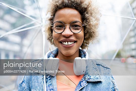 Happy woman wearing wireless headphones holding umbrella - p300m2277426 by Rafael Fernandez Torres
