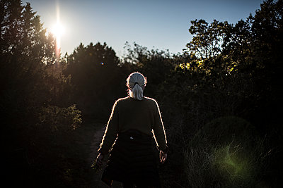 Woman walking in nature to the sun - p1007m1540379 by Tilby Vattard