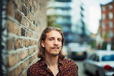Portrait confident young male hipster on urban sidewalk - p1023m2046665 by Paul Bradbury