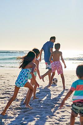 Family playing soccer on sunny ocean beach - p1023m2200888 by Trevor Adeline
