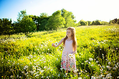 Young Girl With Red Hair in Pink Dress Skipping Through Meadow - p1166m2147173 by Cavan Images