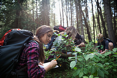 Teenage outdoor school girl student exploring undergrowth in woods, taking notes - p1192m1490890 by Hero Images