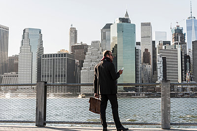 USA, Brooklyn, businessman with briefcase and smartphone standing in front of Manhattan skyline - p300m1205672 by Uwe Umstätter