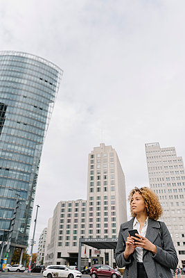 Woman holding smartphone with office buildings in background, Berlin, Germany - p300m2143459 von Hernandez and Sorokina