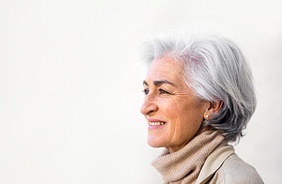 Smiling woman with gray hair contemplating by white wall - p300m2281461 by PICUA ESTUDIO