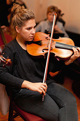 Violin player practicing with group - p429m712168f by Hybrid Images